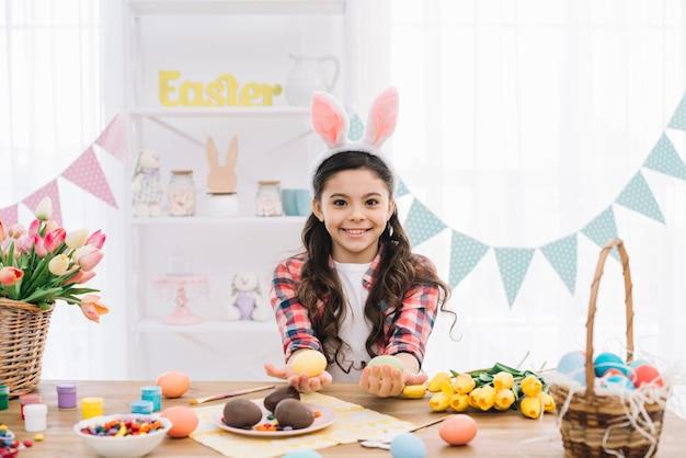 Close-up van een glimlachend meisje die konijntjesoren dragen die kleurrijke paaseieren tonen Gratis Foto