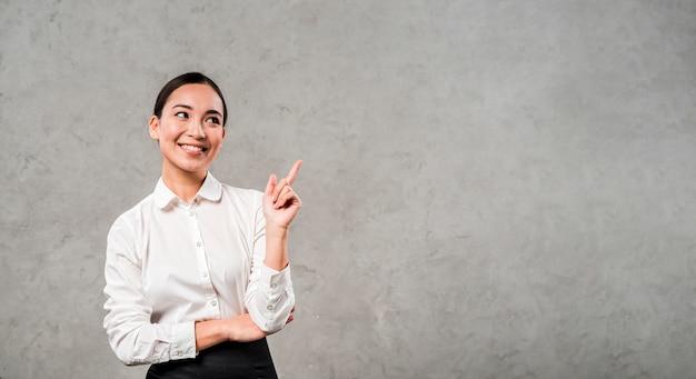 Close-up van een glimlachende jonge onderneemster die haar vinger naar boven richt die zich tegen concrete muur bevindt Gratis Foto