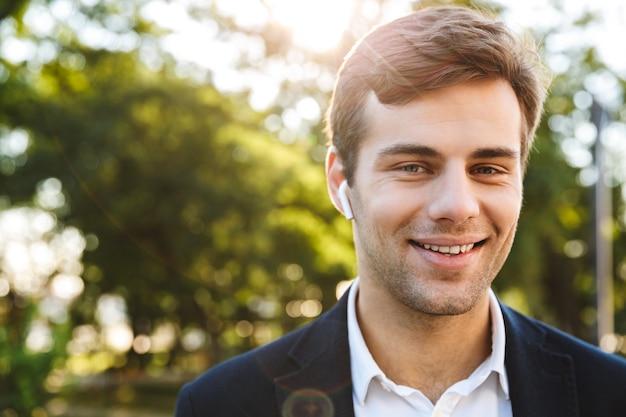Close up van een glimlachende jonge zakenman buiten lopen, het dragen van oortelefoons Premium Foto