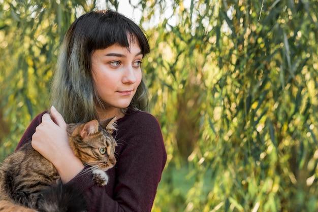 Close-up van een glimlachende mooie vrouw die haar gestreepte katkat in park omhelst Gratis Foto