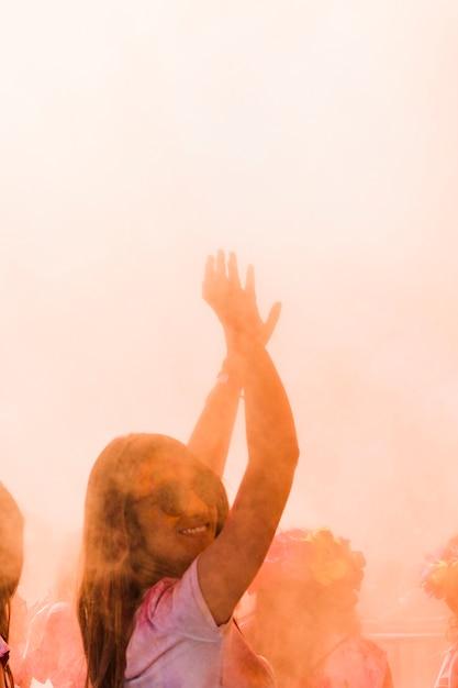 Close-up van een glimlachende vrouw die in de holikleur danst Gratis Foto