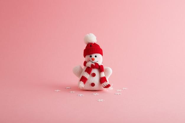 Close-up van een grappige sneeuwman en sneeuwvlokken op de roze achtergrond Gratis Foto