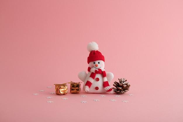 Close-up van een grappige sneeuwman, kleine geschenkdozen en een dennenappel op de roze achtergrond Gratis Foto