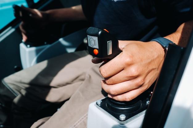 Close-up van een hand die de stuurknuppel vasthoudt en klaar om te werken in de vrachtwagenkraan, de grootste vrachtwagenkraan voor uitdagende taken. Premium Foto