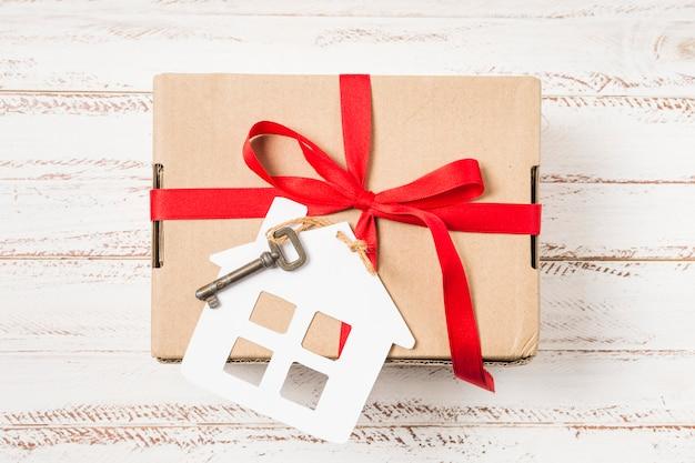 Close-up van een huissleutel die met rood lint op bruine giftdoos wordt gebonden over geschilderd houten bureau Gratis Foto