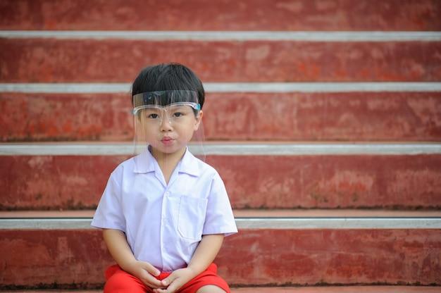Close-up van een jonge aziatische jongen die een gezichtsscherm draagt tegen het coronavirus covid-19 Premium Foto