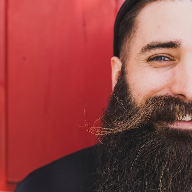 Close-up van een jonge man met snor en baard tegen rode achtergrond Gratis Foto