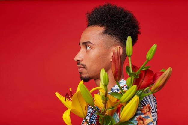 Close-up van een jonge rustige afro-amerikaanse man in hawaiiaans overhemd, houdt gele en rode bloemen boeket, staat op rode achtergrond. Gratis Foto