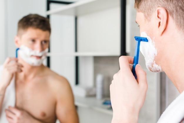 Close-up van een jonge shirtless man scheren met blauw scheerapparaat voor spiegel Gratis Foto