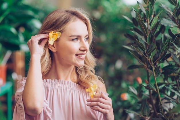 Close-up van een jonge vrouw die de gele bloem plaatst achter haar oor Gratis Foto
