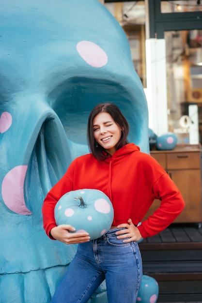 Close-up van een jonge vrouw die een sierlijke pompoen van blauwe kleur op witte vlekken houdt Gratis Foto