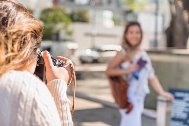 Close-up van een jonge vrouw die haar vrouwelijke vriend met camera fotografeert Gratis Foto