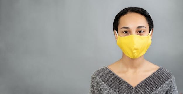 Close-up van een jonge vrouw met een geel masker op haar gezicht tegen sars-cov-2. grijze muur. kopieer ruimte. kleurentrends van 2021. positief concept Premium Foto
