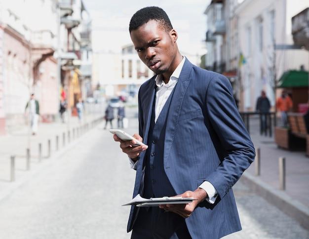 Close-up van een jonge zakenman klembord in de hand houden met behulp van de mobiele telefoon Gratis Foto