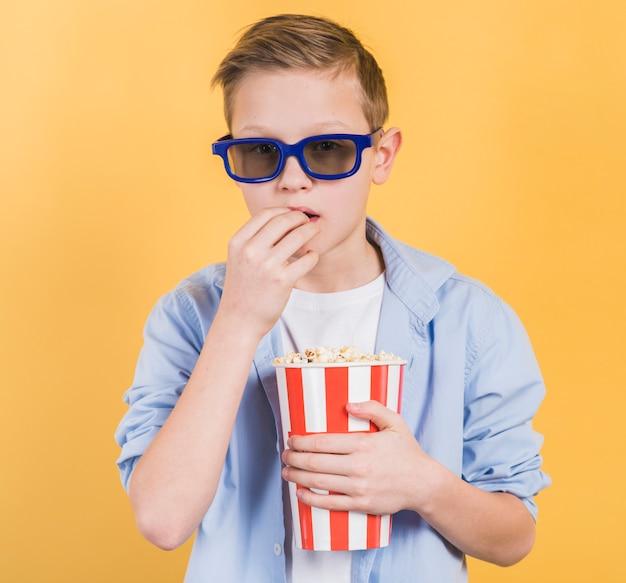 Close-up van een jongen die blauwe 3d glazen draagt die popcorns eten tegen gele achtergrond Gratis Foto