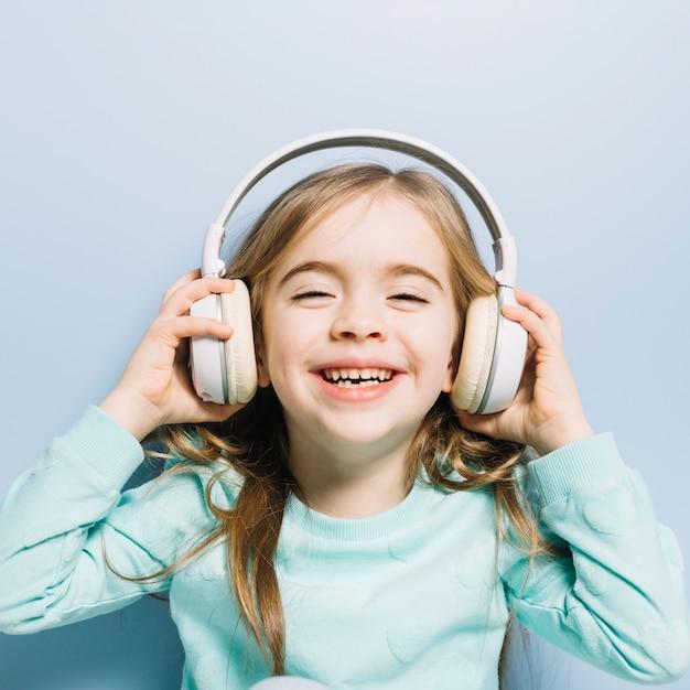 Close-up van een klein glimlachend meisje dat van de muziek op hoofdtelefoon geniet Gratis Foto