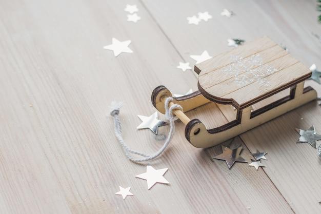 Close-up van een klein houten slee-ornament op de tafel onder de lichten Gratis Foto