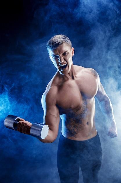 Close-up van een knappe bodybuilder die van de machts atletische mens oefeningen met domoor doen. geschiktheids gespierd lichaam op donkere rookachtergrond. perfecte reu. geweldige bodybuilder, tattoo, poseren. Premium Foto