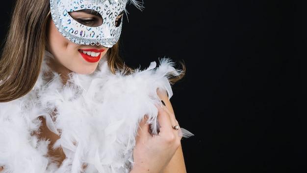 Close-up van een lachende vrouw met carnaval masker en boa veer op zwarte achtergrond Gratis Foto