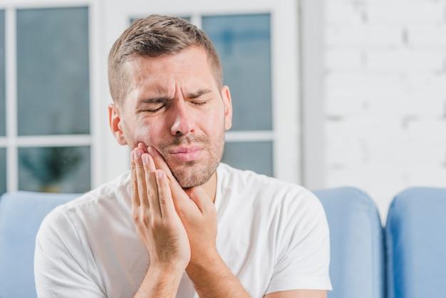 Close-up van een man die aan tandpijn lijdt Premium Foto