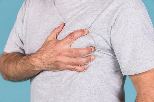 Close-up van een man hand met zijn hart in pijn Gratis Foto
