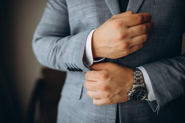Close-up van een man in een smoking die zijn manchetknoop bevestigt Premium Foto