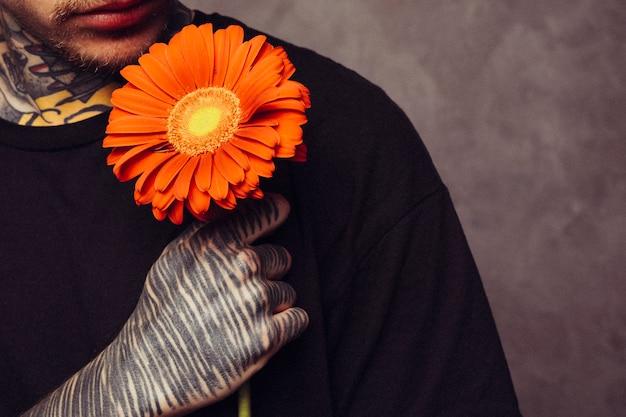 Close-up van een man met tatoeage op zijn hand met een oranje gerberabloem over schouder Gratis Foto
