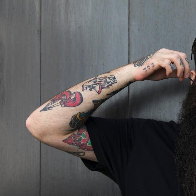 Close-up van een man met tatoeage op zijn hand staande tegen grijze houten muur Gratis Foto