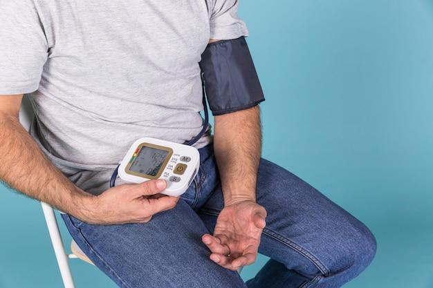 Close-up van een man zittend op een stoel het controleren van de bloeddruk op een elektrische tonometer Gratis Foto