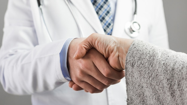 Close-up van een mannelijke arts en een patiënt handen schudden Gratis Foto
