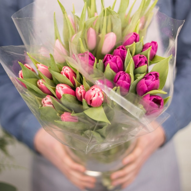 Close-up van een mannelijke bloemist die het roze boeket van de tulpenbloem houdt Gratis Foto