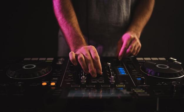 Close-up van een mannelijke dj die werkt onder de lichten tegen een donkere achtergrond in een studio Gratis Foto