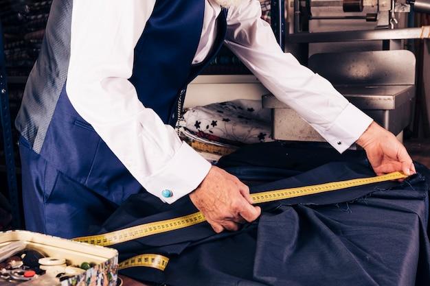 Close-up van een mannelijke kleermaker die meting van stof met gele metende band neemt Gratis Foto