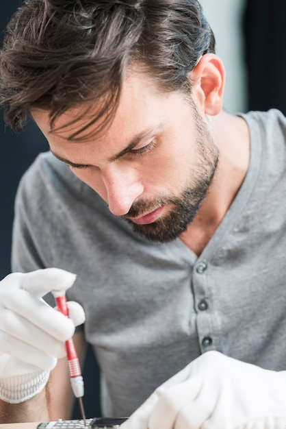 Close-up van een mannelijke technicus die gebroken mobiele telefoon herstelt Gratis Foto