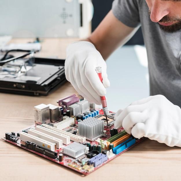 Close-up van een mannelijke technicushand die computermotherboard op houten bureau herstellen Gratis Foto