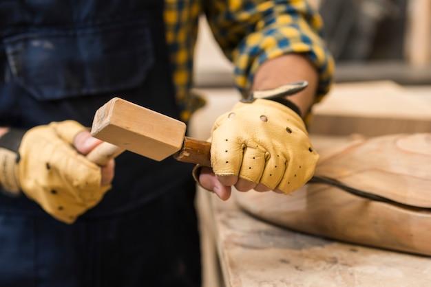 Close-up van een mannelijke timmerman die beitel op houten structuur met hamer raken Gratis Foto