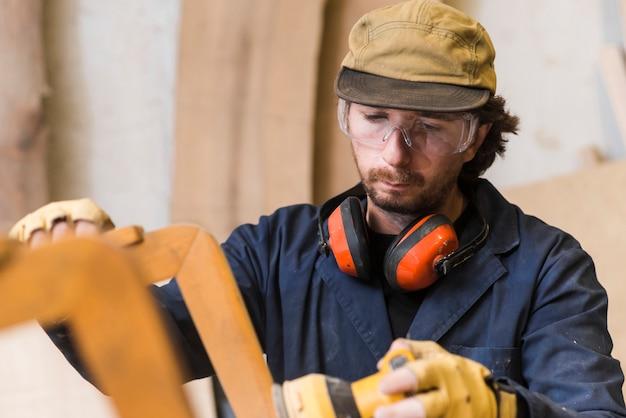 Close-up van een mannelijke timmerman die veiligheidsbril en oorverdediger draagt rond zijn hals die elektrische schuurmachine met behulp van Gratis Foto