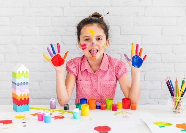 Close-up van een meisje dat haar tong uitsteekt die haar twee geschilderde handen toont Gratis Foto