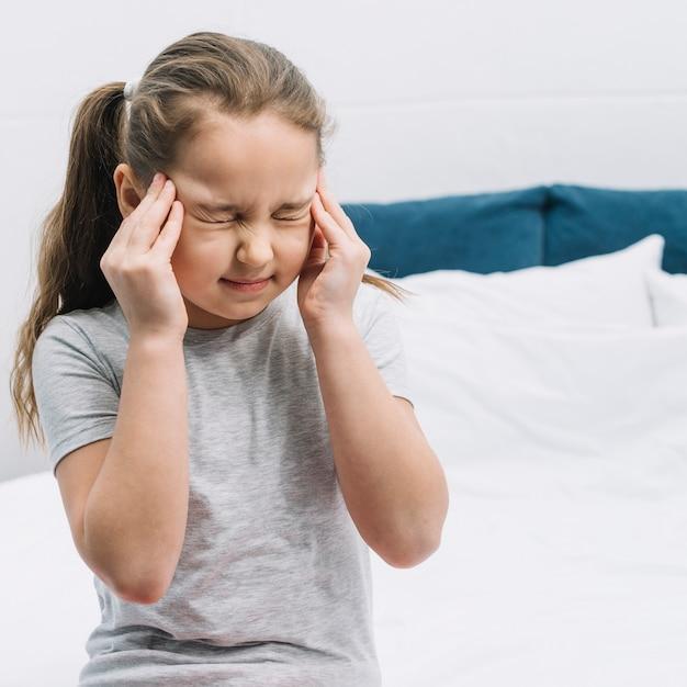 Close-up van een meisjeszitting op bed die pijn in hoofdpijn hebben Gratis Foto