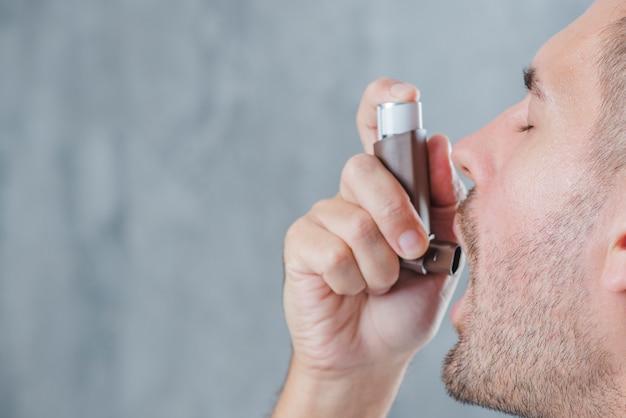 Close-up van een mens die astmainhaleertoestel met behulp van tegen onduidelijk beeldachtergrond Gratis Foto