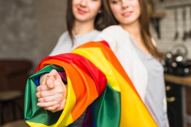 Close-up van een mooi lesbisch jong paar die elkaar handen met verpakte lgbt trotsvlag houden Gratis Foto