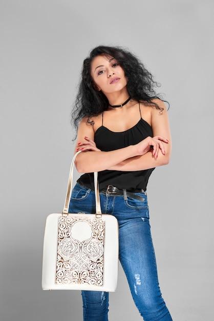 Close-up van een mooi sexy meisje met zwart krullend haar, dat er erg modieus uitziet in haar spijkerbroek, zwarte top, leren riem en chocker om haar nek. ze draagt een witte tas Gratis Foto