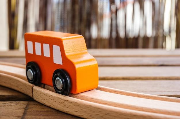 Close-up van een oranje houten speelgoedauto op de sporen onder de lichten Gratis Foto