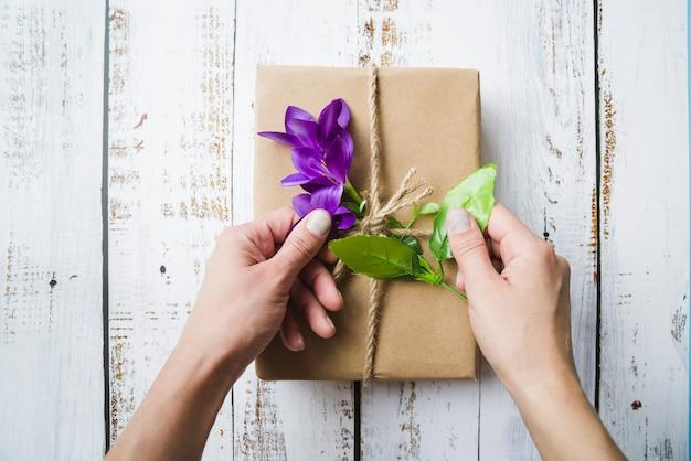 Close-up van een persoon die de bloemen op het ingepakte pakket raakt Gratis Foto