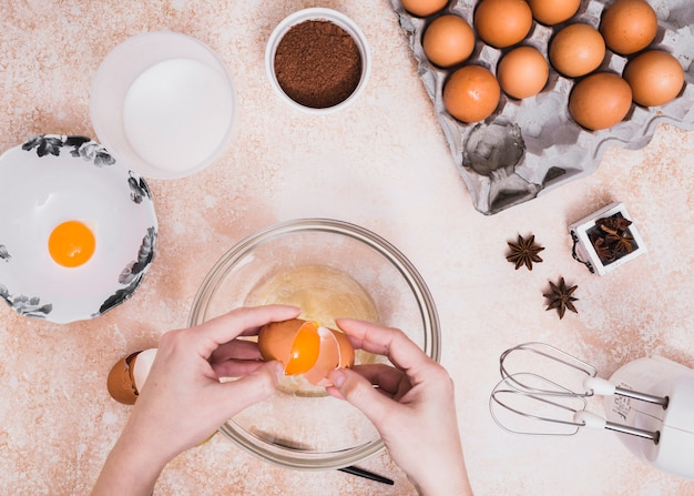 Close-up van een persoon die de eieren in de glaskom breekt voor het maken van het cakedeeg Gratis Foto