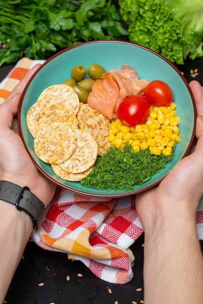 Close-up van een persoon die een kom salade met zalm, crackers en groenten onder de lichten houdt Gratis Foto