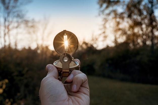 Close-up van een persoon die een kompas met zon houdt die door het gat glanst Gratis Foto