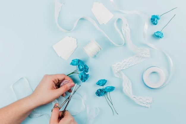 Close-up van een persoon die het lint met schaar voor het binden van de blauwe rozen op gekleurde achtergrond snijdt Gratis Foto