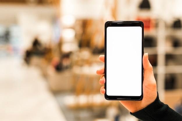 Close-up van een persoon slimme telefoon die het witte vertoningsscherm toont tegen vage achtergrond Gratis Foto