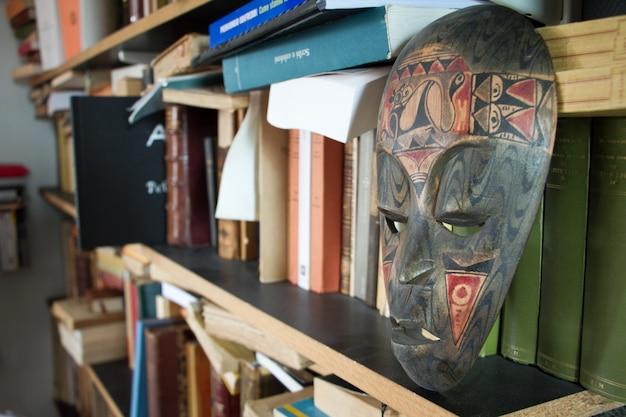 Close-up van een plank met boeken en een antiek masker in een klein appartement in de buitenwijken van parijs Premium Foto